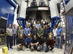 Das LN-Team nach erfolgreicher Begutachtung des LINC-NIRVANA-Instruments mit erkennbar großen Ausmaßen im Hintergrund.