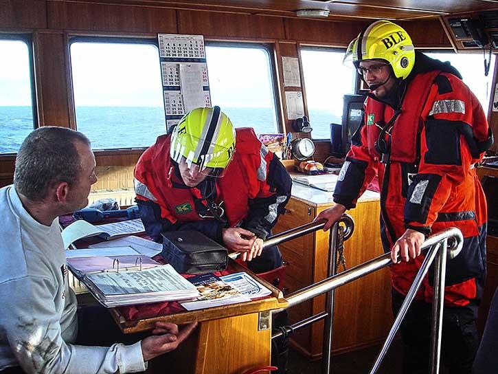 Vom Kapitän des Kutters erhalten die Inspektoren Einblick in die Schiffspapiere.