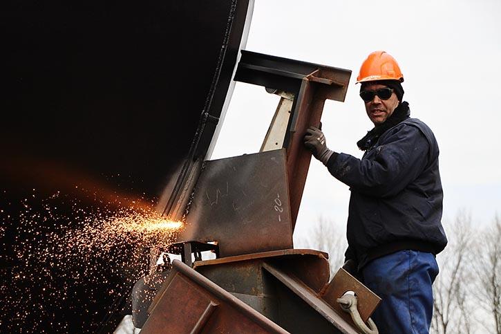 Werftarbeiter brennen die letzte Halterung zwischen Schiff und Helgen ab.
