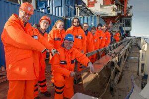 Polarsternfahrtleiter Prof. Dr. Rüdiger Stein und sein Team posieren neben dem Kastenlot, welches den Sedimentkern enthält.