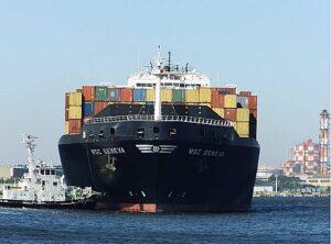 Beladenes Containerschiff mit Schlepper.