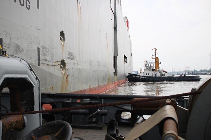 Mit vereinten Kräften wird der Autotransporter an die Pier bugisert.