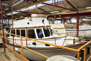 In den großräumigen Werfthallen liegen mehrere Yachten in GFK-Bauweise zu Wartungsarbeiten.