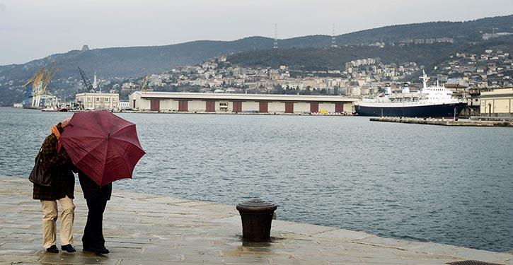 Spaziergänger mit Regenschirm im Hafen von Triest. Im Hintergrund befindet sich der alte Seehafen.