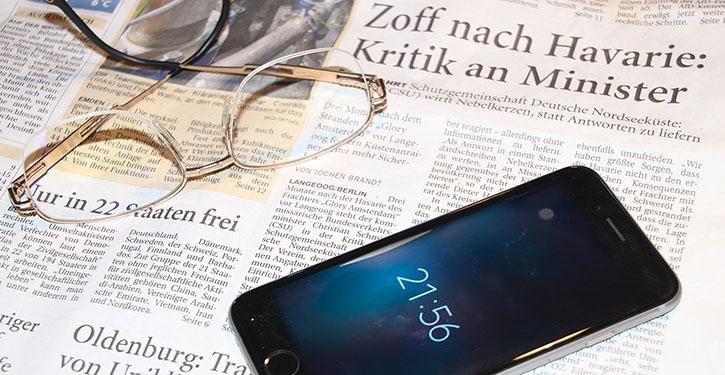 Zeitungsausschnitt mit Mobiltelefon und Brille.