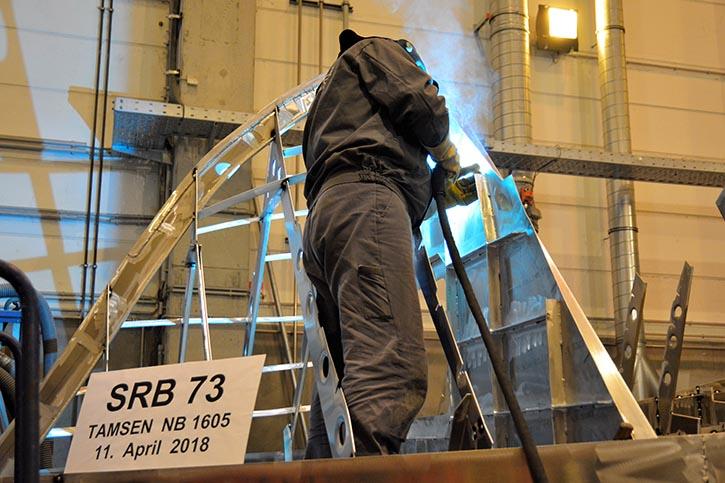 Ein Werftarbeiter schweißt am Seenotrettungsboot SRB 73 die Kieltasche zu.