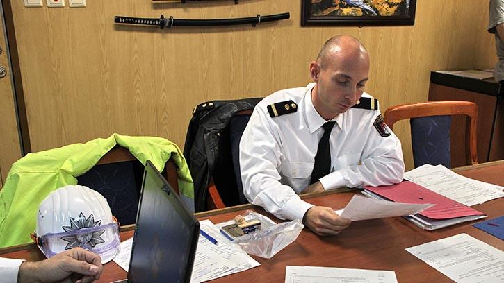 Beamter der Wasserschutzpolizei kontrolliert die Schiffstagebücher. © Pospiech