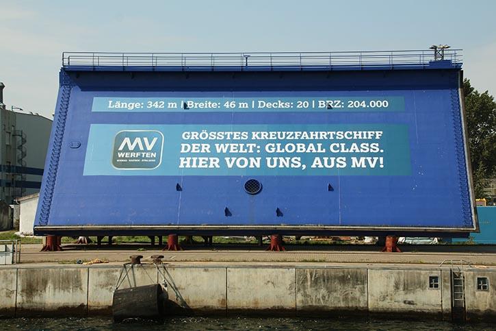 """An der Kaikante in Warnemünde wirbt MV Werften auf einem Stahlschild für die """"Global Class"""""""